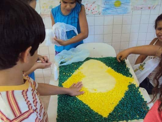 crianças montando a bandeira do Brasil com papel crepom