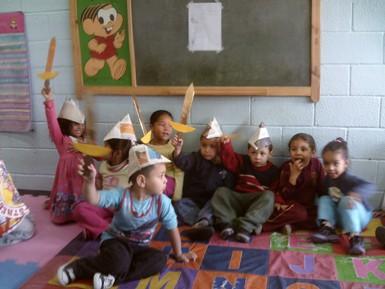 crianças usando chapéu e espadinhas de jornal