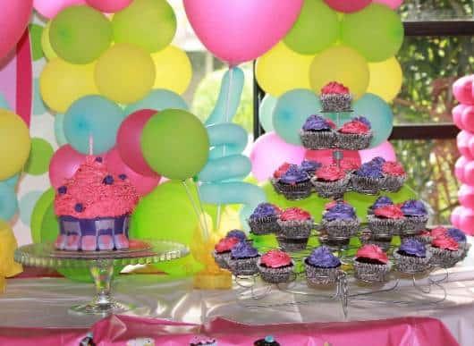 lindo bolo cupcake com balões amarelo azul e rosa ao fundo