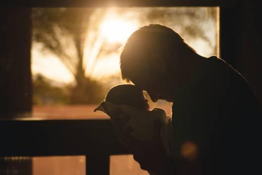 Pai encostando a sua testa na testa do seu bebê.