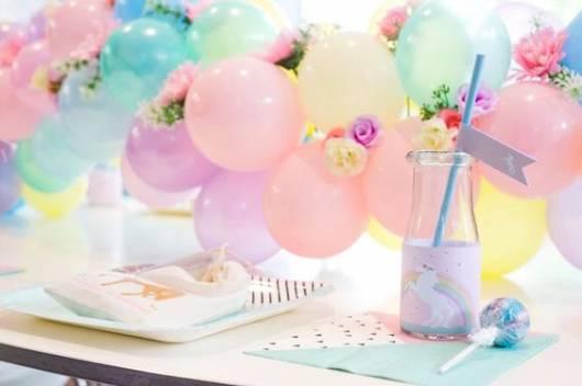 Mesa decorada com pratinho listrado e copo com adesivo de unicórnio.