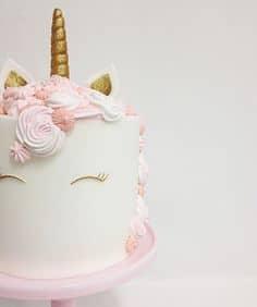 Bolo de unicórnio com as cores rosa, branco e dourado.