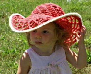 Menina em um jardim com chapéu de sol em crochê na cor goiaba