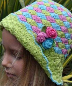 menina com chapeu colorido em azul, rosa e verde com aplique de tres mini rosass