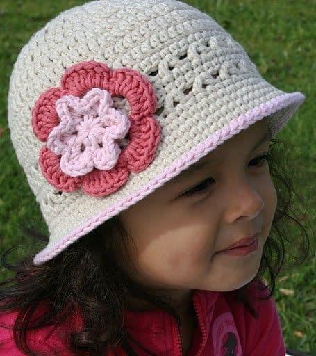 menina com chapéu de crochê na cor cru com aplique de rosa em dois tons rosados