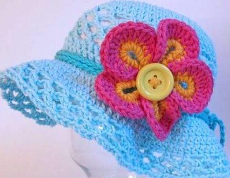 chapéu azul com cordão em crochê e aplique de flor com botão no centro representando o miolo