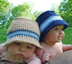 dois bebês usando chapéu de crochê. um na cor cru e outro a cor azul escuro, ambos com faixas azuis