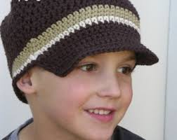 garoto com boné de crochê na cor marrom com detalhe no crochê nas cores bege e braco