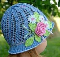 menina em jardim com chapéu azul claro com detalhe de uma rosa com folhagem