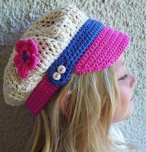 menina loira com chapéu de crochê no modelo d boné na cor cru com aplique de uma rosa, aba rosa e detalhes em azul