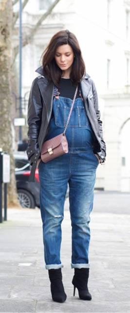 Look com macacão jeans para gestante, jaqueta de couro e bolsa em tom rosê.