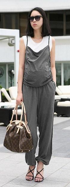 Look com macacão gestante cinza, bolsa e sandália preta.