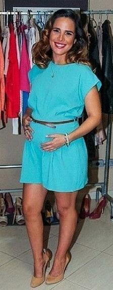 Vanessa Camargo, veste macaquinho azul claro com cintinho e sandália de salto.