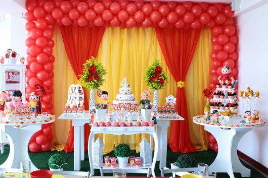 Decoração de festa da Magali com móveis provençais e fundo amarelo e vermelho.