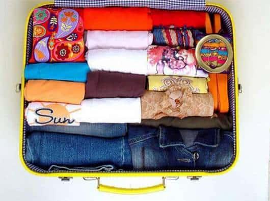 Mala organizada com roupas em rolinhos.