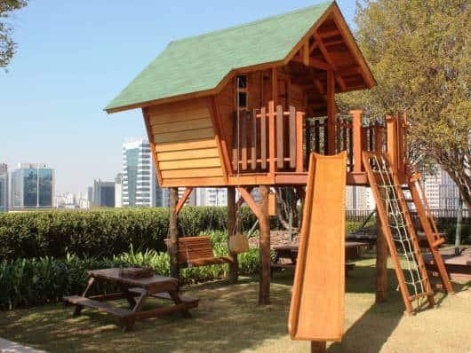 Playground com rede de escalada, escorregador e mesa de piquenique.