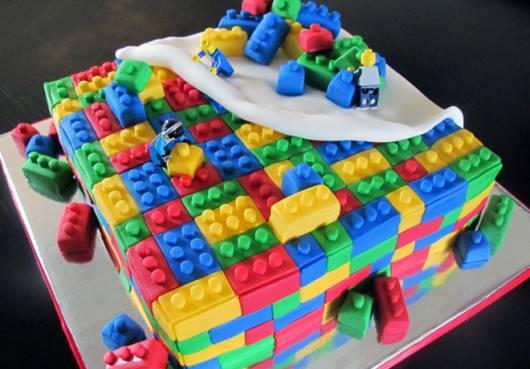 Bolo lego com algumas peças coloridas espalhadas.