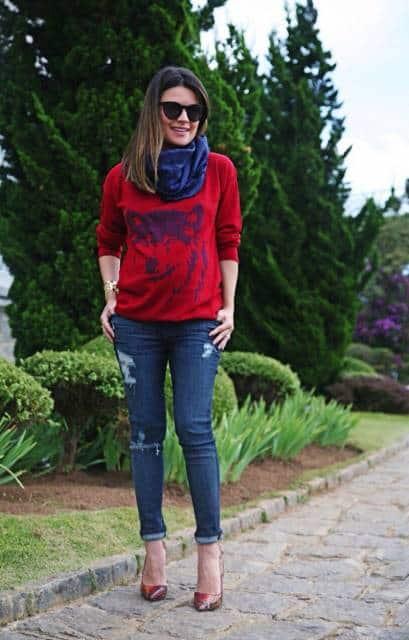 Modelo veste blusa vermelha, lenço azul escuro, calça jeans e sapato vermelho de salto.