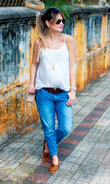 Modelo veste calça jeans boyfriend, blusa branca de alcinha, sapatilha em tons de terra e bolsa nude.