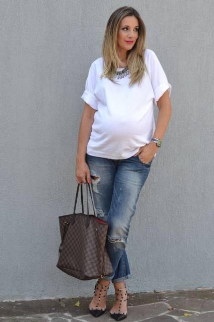 Modelo veste calça jeans destroyed cinza, sapatilha com spikes, blusa branca e bolsa marrom de mão.