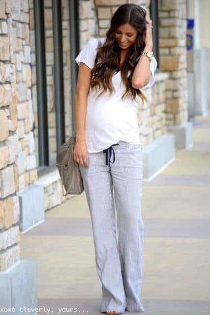 Modelo usa look com calça de malha cinza, blusa branca e sapato.