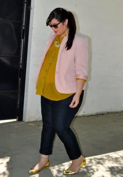 Modelo veste calça jeans,sapatilha dourada, camisa no mesmo tom e blazer rosa bebê.