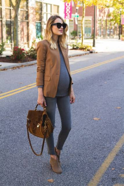 Modelo veste calça jeans cinza, blusa no mesmo tom, sapato, bolsa de mão e blazer cor terra.