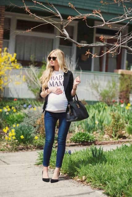 Modelo grávida veste, calça jeans azul, blusa básica branca,sapato, bolsa de mão e blazer preto.