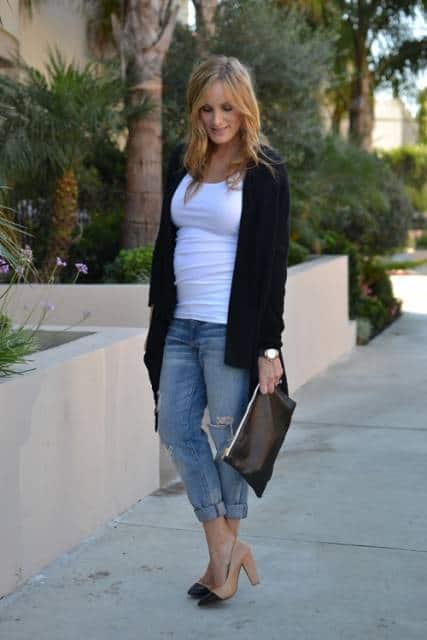 Modelo veste look com calça jeans cigarrete, blusa branca, sapato terra com a ponta em tom de preto, bolsa de mão e sobreposição preta.