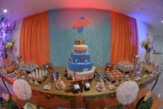 Mesa principal e painel decorados em azul claro e laranja.