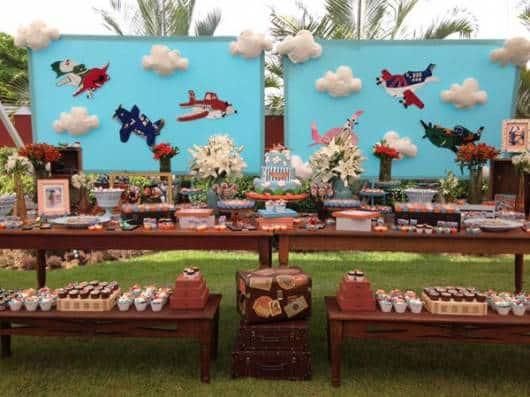 Decoração com painel de céu azul, aviões e nuvens.