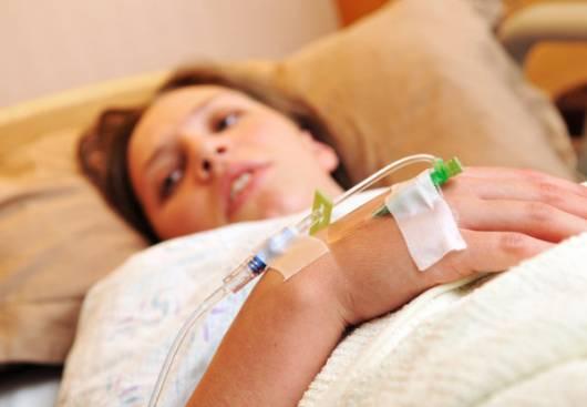 Mãe deitada com acesso na mão, aguardando a indução de parto.