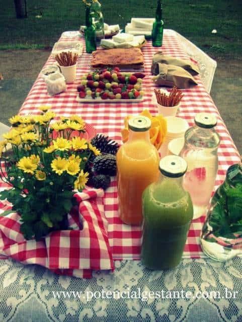 Mesa de piquenique com suco e comida.