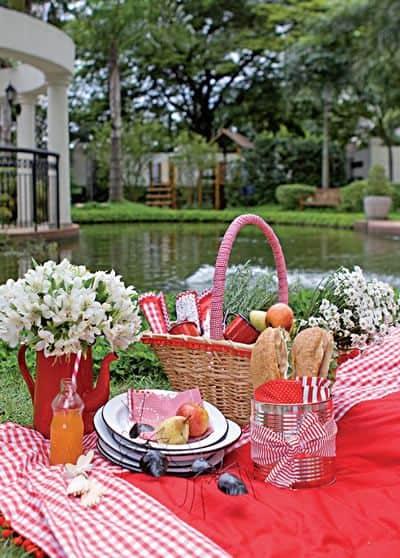 Cesta, pratos, frutas, suco e flores em cima da mesa.