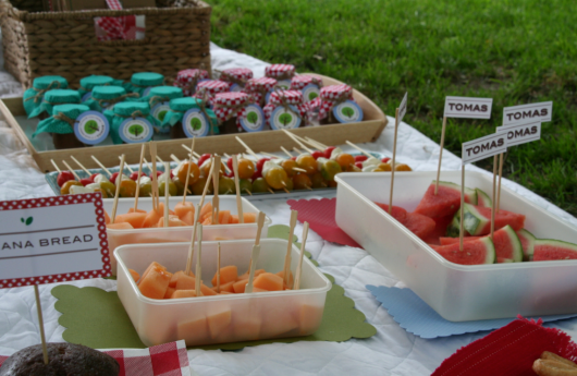 Várias frutas no palito e comida em potes.