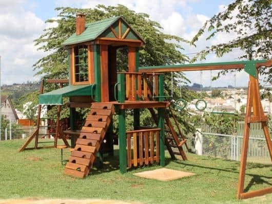 Playground de madeira com algumas tábuas em verde.