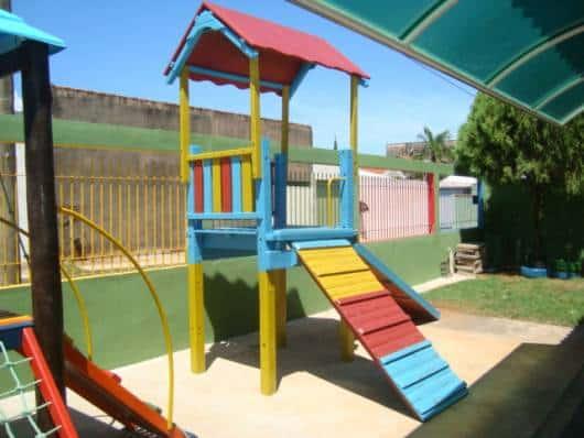 Playground simples de madeira, nas cores amarelo, vermelho e azul.