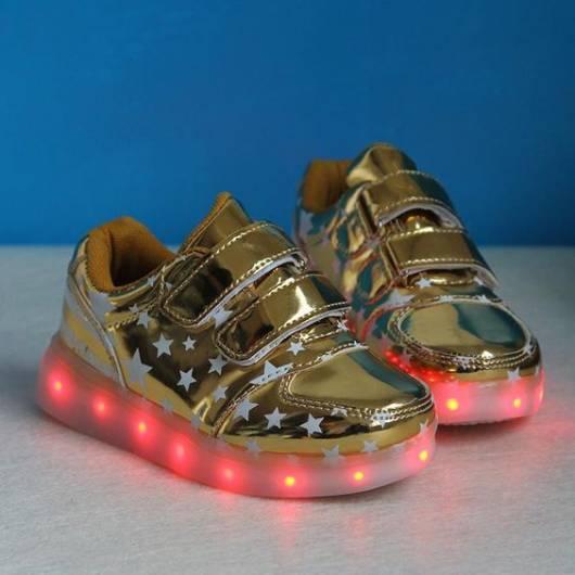 tênis dourado com estrelas