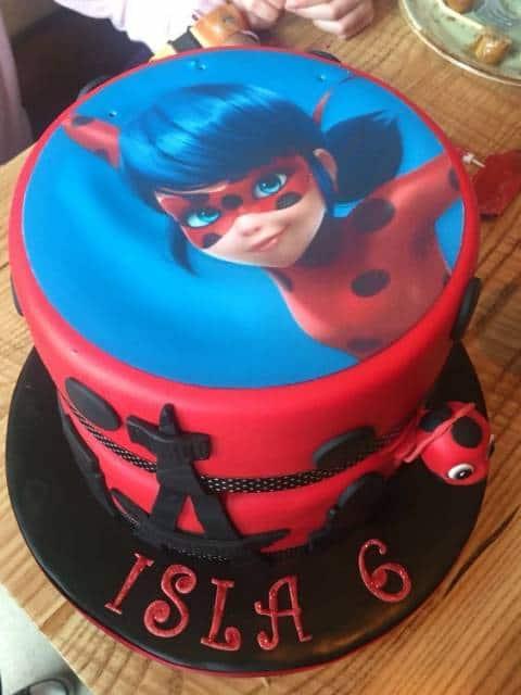 Imagem da Ladybug com fundo azul no topo do bolo vermelho.