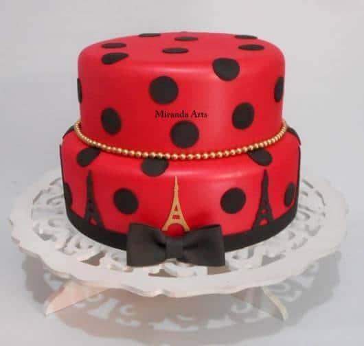 Bolo de duas camadas com cobertura vermelha, bolas, laços e torres em preto e bolinhas e uma Torre Eiffel em dourado.