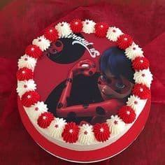 Bolo vermelho com desenho da Ladybug no topo e com decoração de chantilly na borda.