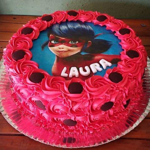 Bolo com glacê vermelho e imagem da Ladybug em cima.