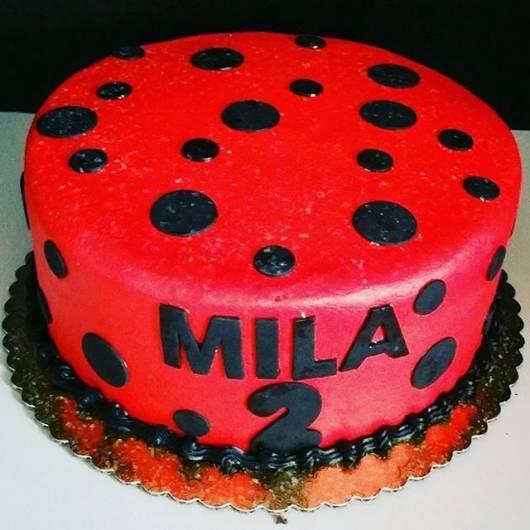 Bolo vermelho com bolas, nome e idade em preto.