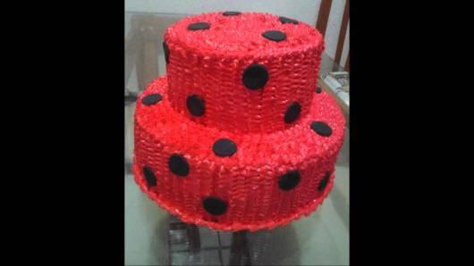 Bolo de dois andares decorado com glacê vermelho e círculos pretos.