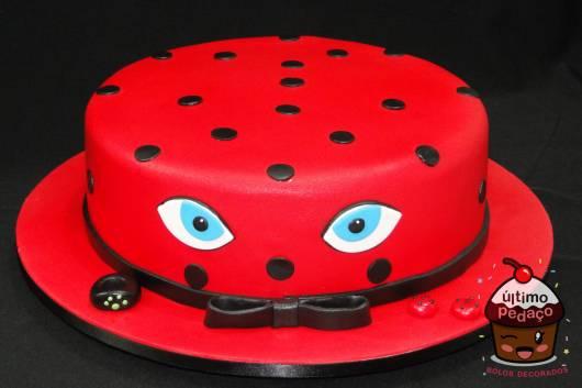 Bolo vermelho com bolas e laço preto e olhos azuis da Ladybug.