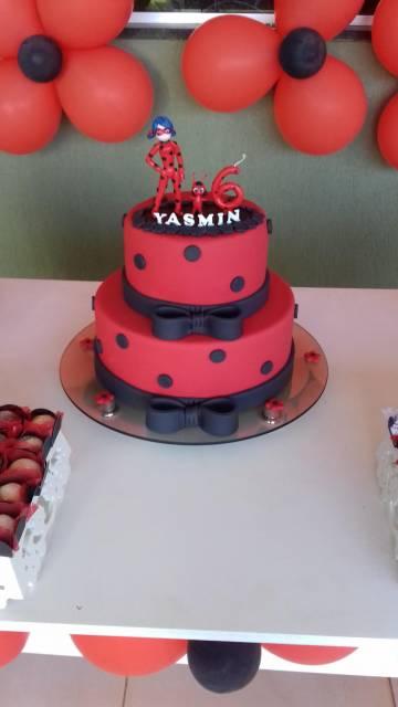 Bolo Ladybug vermelho com bolas e laços pretos e personagem, vela e nome no topo.