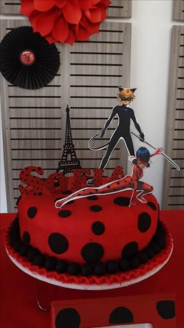 Bolo vermelho com bolinhas pretas e desenho da Ladybug, Cat Noir e da torre Eiffel em cima.