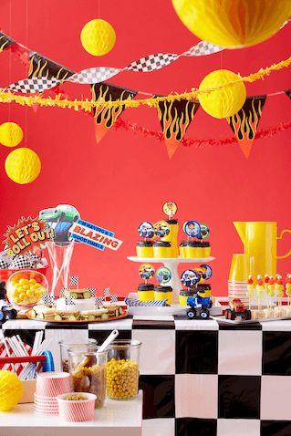 Decoração de festa com fundo vermelho e toalha de mesa preta e branca.