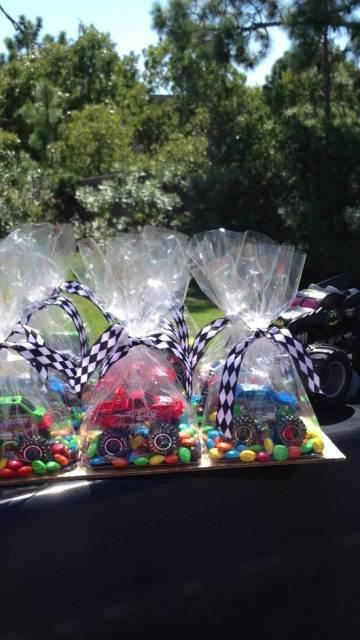 Pacotes de lembrancinhas com doces e carrinhos.