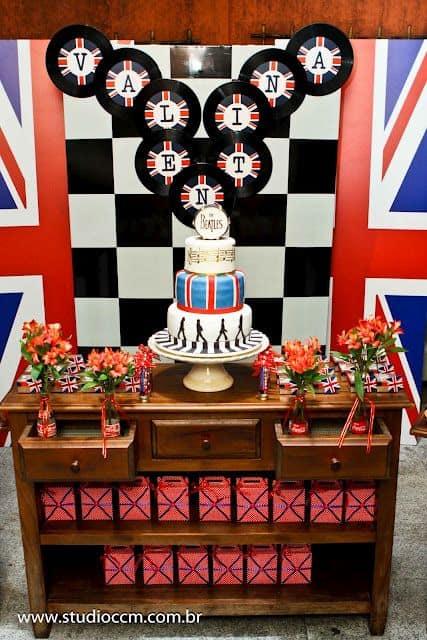 Festa Rock n' Roll com bandeira da Inglaterra no fundo da mesa do bolo.